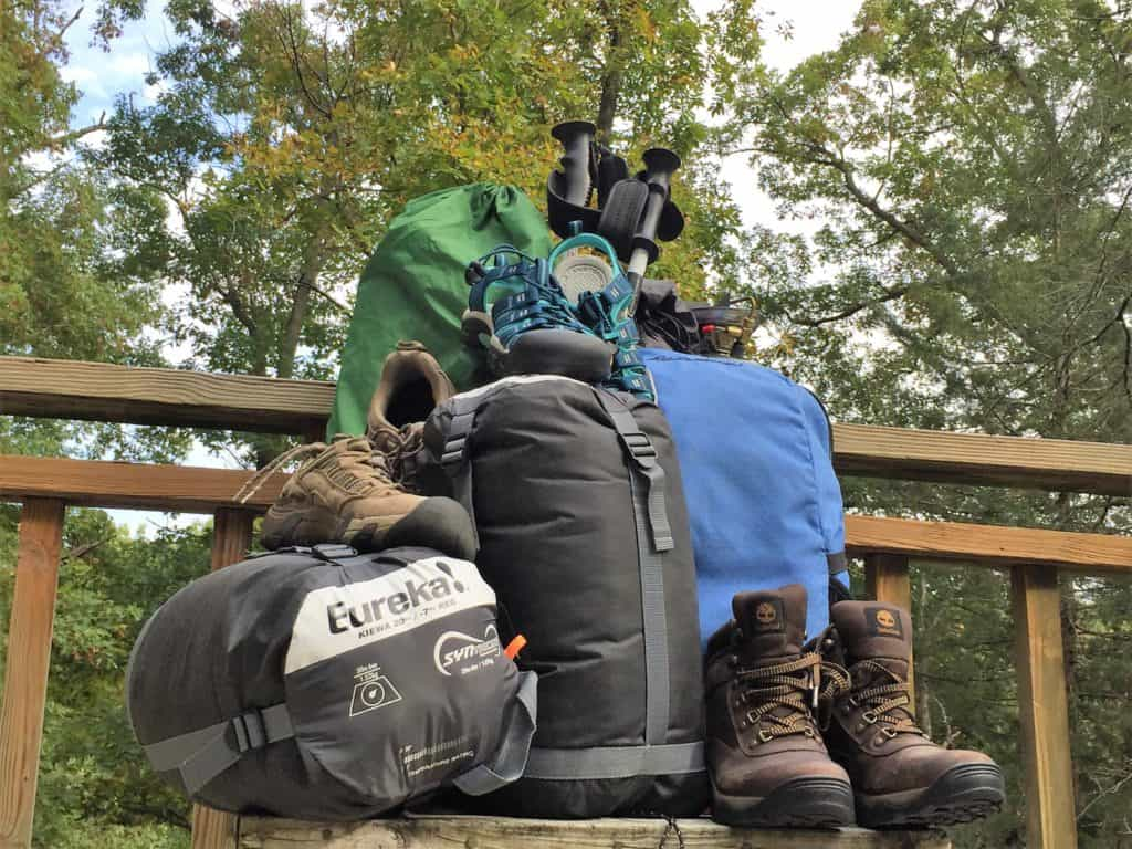 camping and hiking gear piled up on a deck