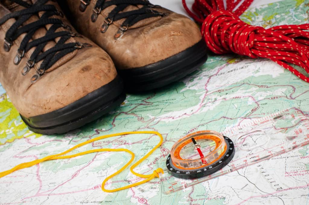 compass and map with hiking shoes, critical for day hiking packing list