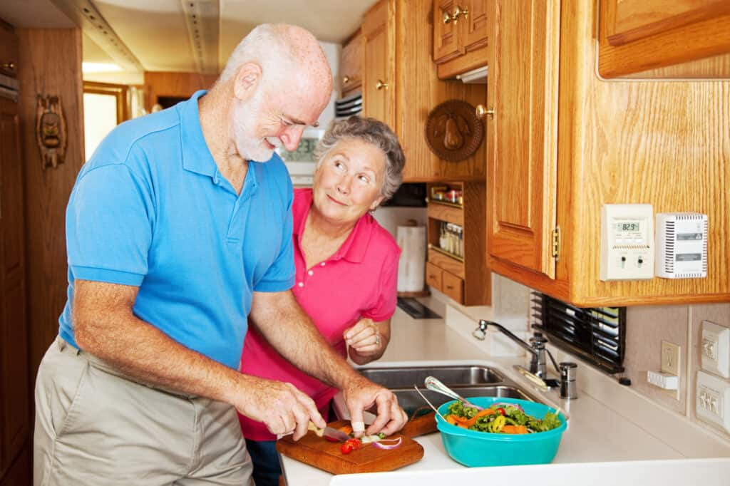 Couple cooking in camper, kitchen gifts make the best gifts for RV owners