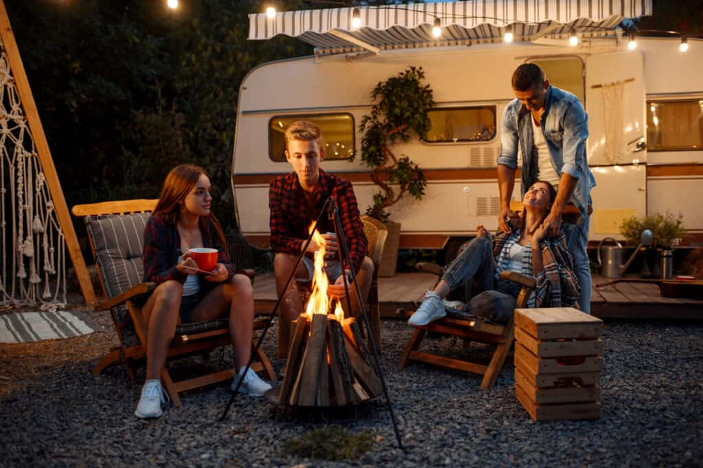 Friends gathered in front of camper enjoying best gifts for RV Owners