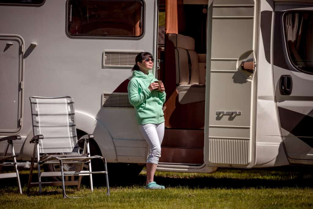 Woman enjoying gift of morning coffee in front of RV Camper