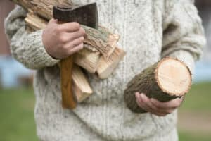 Man with firewood and camping hatchet