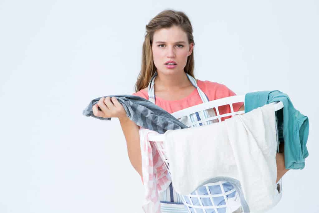Woman holding laundry basket wondering how to wash merino wool