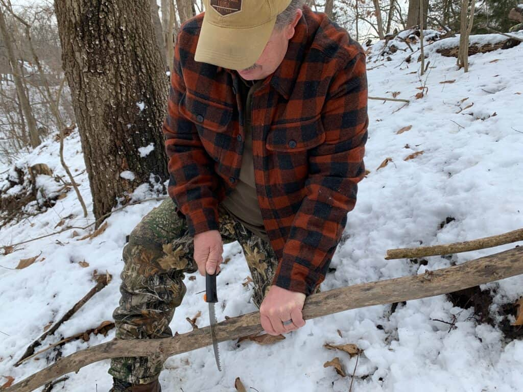 Brad cutting tree branch with folding camping saw