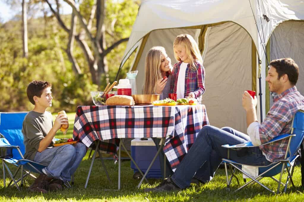 Family sitting at folding camping table with plaid table cloth and food on it