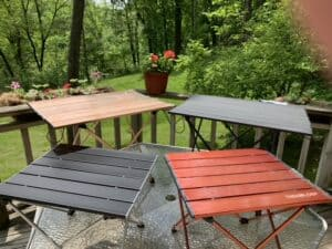 Four styles of folding side tables for camping sitting on a table
