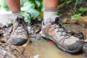 Wet hiking shoes in a puddle after a hike in the rain