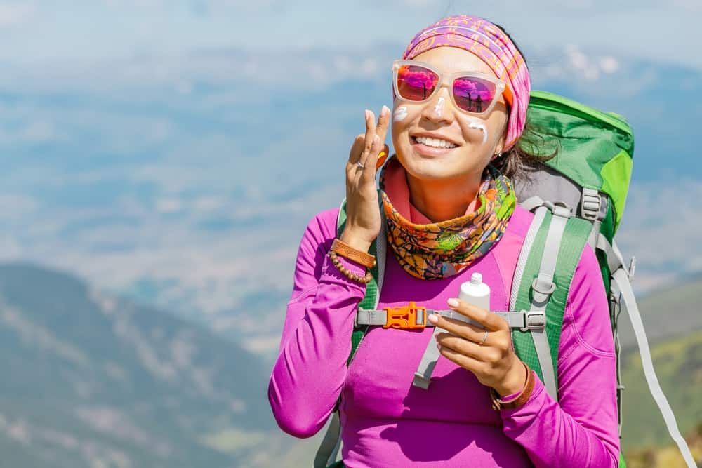 woman hiker applying sunscreen while hiking in the heat
