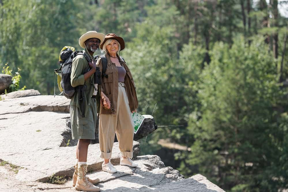 Couple standing on rock ledge dressed for hot weather hiking
