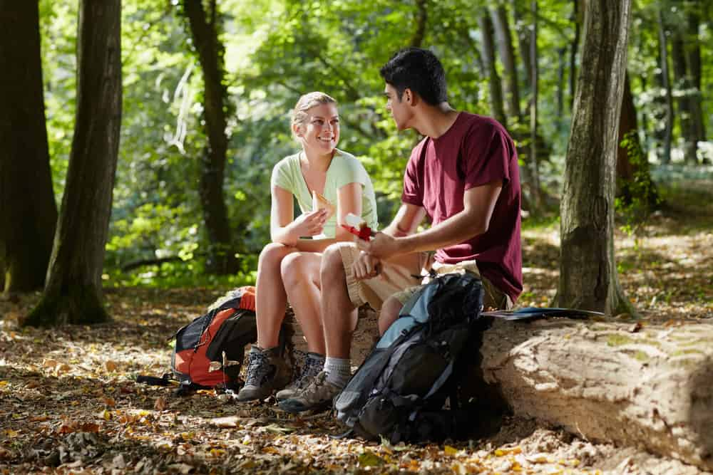 Couple sitting on log taking a break from hiking in hot weather